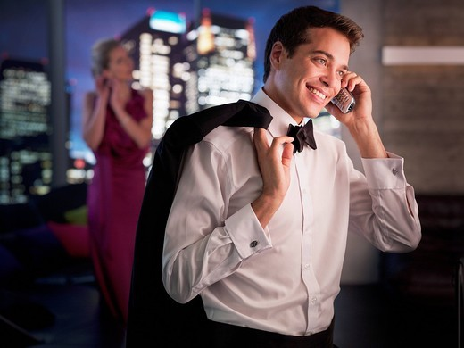 Stock Photo: 1775R-22535 Man in tuxedo talking on cell phone with wife in background