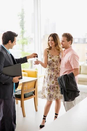 Realtor handing couple keys to home : Stock Photo