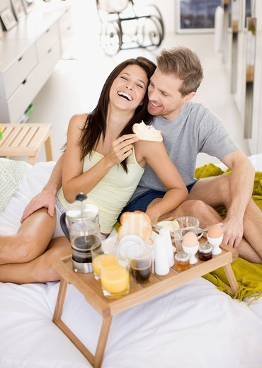 Stock Photo: 1775R-22540 Happy couple having breakfast in bed