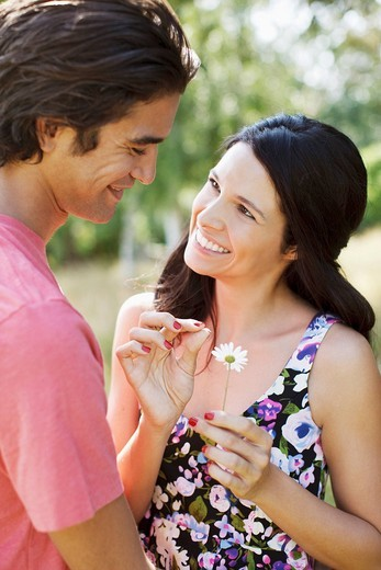 Stock Photo: 1775R-22641 Smiling couple plucking petals from daisy
