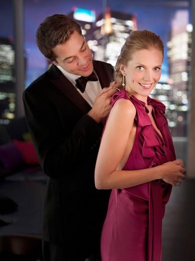 Husband in tuxedo fastening elegant wife's necklace : Stock Photo
