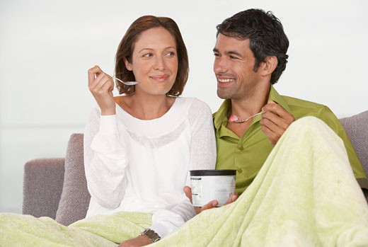 Stock Photo: 1775R-2269 Man and woman on sofa eating ice cream smiling