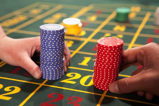 People placing bets with gambling chips : Stock Photo