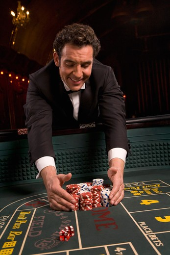 Stock Photo: 1775R-23000 Man gathering winnings at craps table