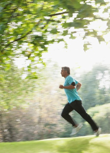 Determined man running outdoors : Stock Photo