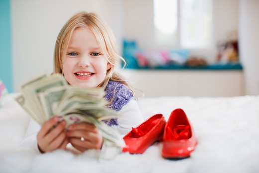 Smiling girl holding dollar bills : Stock Photo