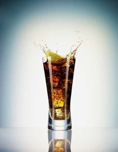Lemon slice splashing soda from glass : Stock Photo