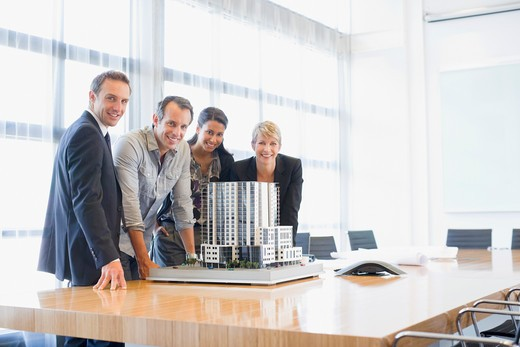 Business people looking at model building in conference room : Stock Photo