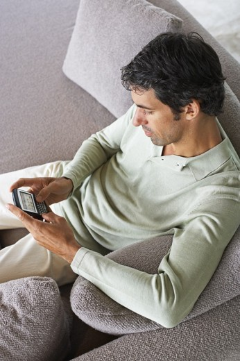 Man sitting on sofa with PDA : Stock Photo