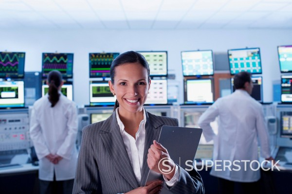 Stock Photo: 1775R-23570 Businesswoman and scientists standing in control room