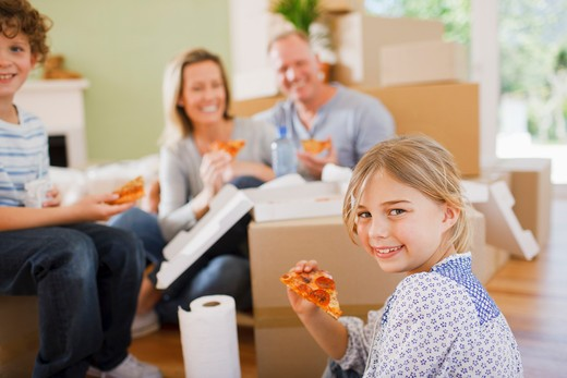 Stock Photo: 1775R-23639 Family eating pizza on the floor in their new house