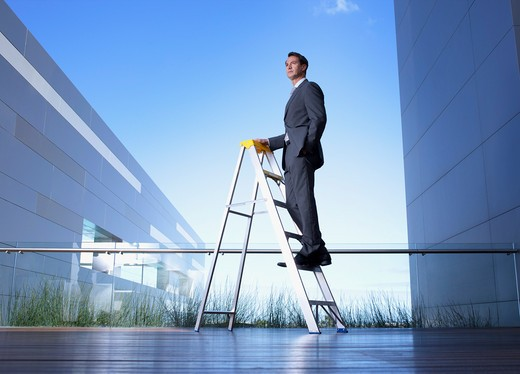 Businessman standing on ladder on balcony : Stock Photo