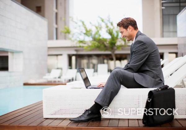 Businessman using laptop on lounge chair near swimming pool : Stock Photo