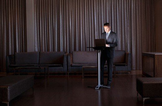 Stock Photo: 1775R-23809 Businessman standing with glowing laptop in hotel lobby