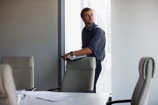 Businessman standing with laptop in conference room : Stock Photo