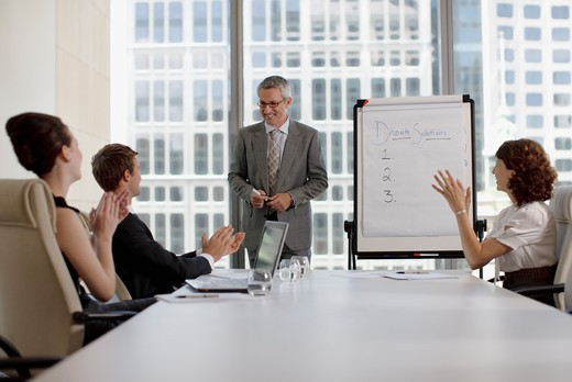 Businessman explaining flip chart to co_workers in conference room : Stock Photo