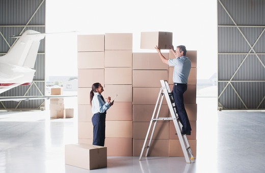 Workers stacking cardboard boxes in hangar : Stock Photo