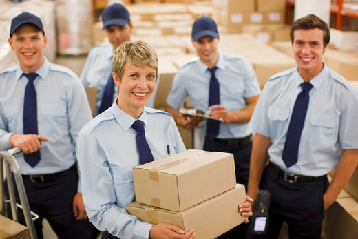Workers with boxes in shipping area : Stock Photo