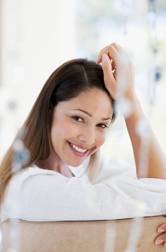 Smiling woman with head in hands : Stock Photo