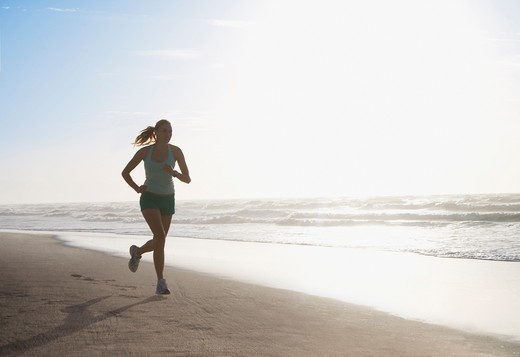 Woman running on beach : Stock Photo