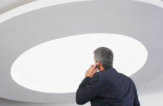 Rear view of businessman talking on cell phone with ceiling light : Stock Photo