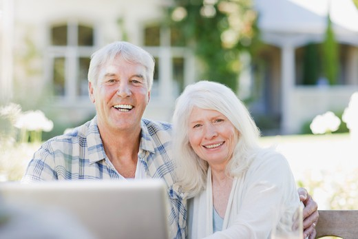 Senior couple using laptop on patio : Stock Photo