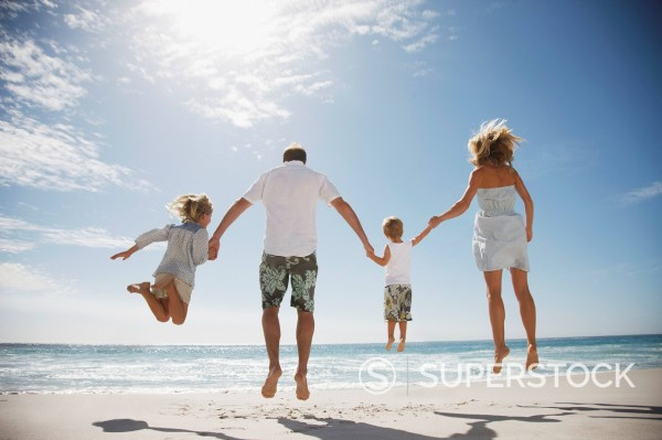 Family holding hands and jumping on beach : Stock Photo