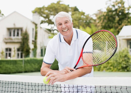 Senior man with racket and ball on tennis court : Stock Photo