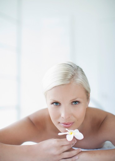 Stock Photo: 1775R-25370 Woman laying on massage table and holding orchid