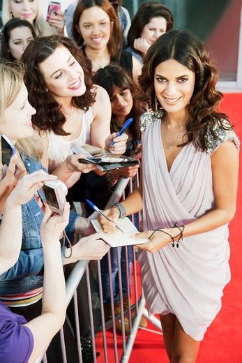 Stock Photo: 1775R-25517 Celebrity signing autographs on red carpet