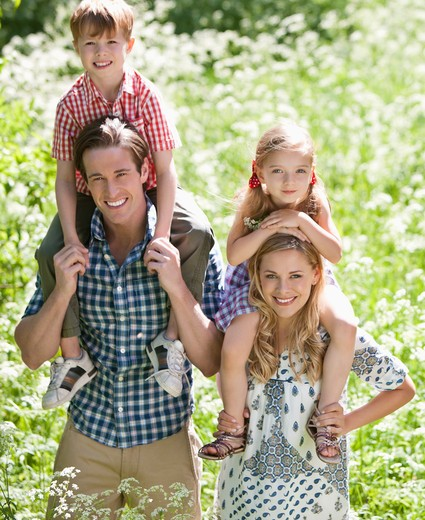 Stock Photo: 1775R-25537 Parents holding children on shoulders in park