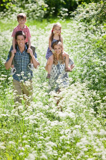 Parents carrying their children piggyback outdoors : Stock Photo