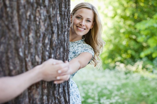 Couple holding hands around tree : Stock Photo