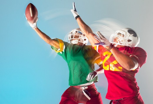 Stock Photo: 1775R-25776 Blurred view of football players grabbing ball