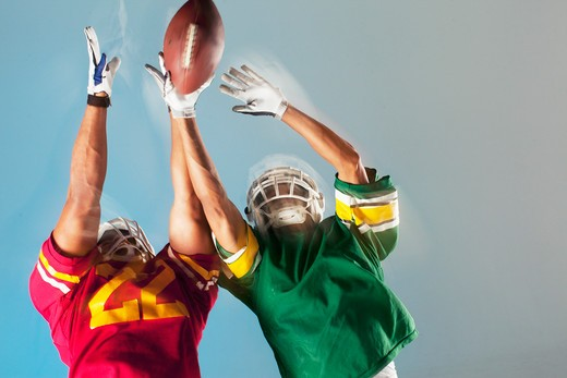 Stock Photo: 1775R-25828 Blurred view of football players reaching for ball