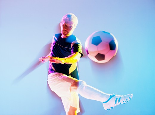 Blurred view of soccer player kicking ball : Stock Photo