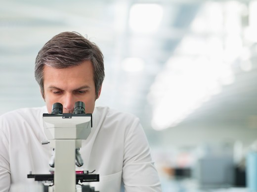 Stock Photo: 1775R-25989 Scientist using microscope in lab