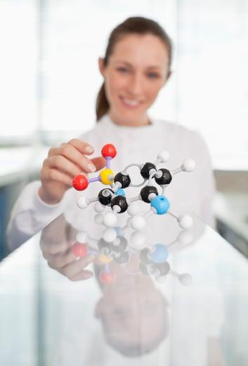 Scientist examining molecular model in lab : Stock Photo