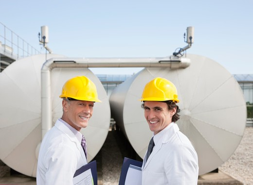 Scientists standing by tanks outdoors : Stock Photo