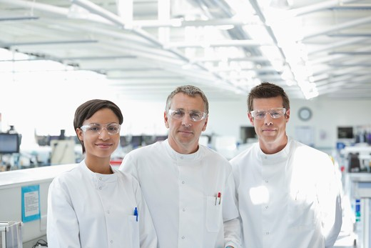Scientists in protective glasses smiling in lab : Stock Photo