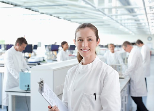 Scientist with clipboard in lab : Stock Photo