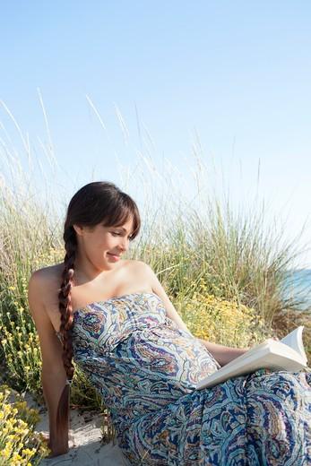 Stock Photo: 1775R-26349 Pregnant woman reading book on beach