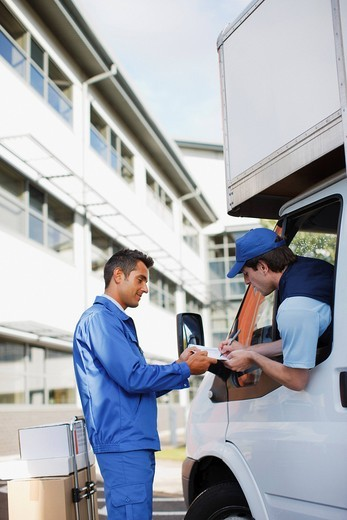 Stock Photo: 1775R-26672 Deliveryman signing clipboard