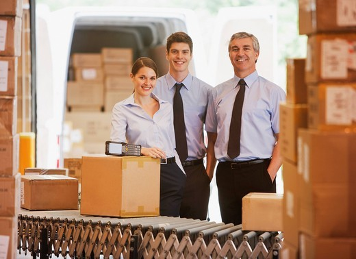Business people standing with boxes in shipping area : Stock Photo