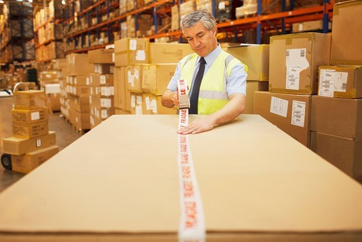 Stock Photo: 1775R-26713 Worker taping box in warehouse