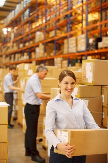 Workers packing boxes in warehouse : Stock Photo