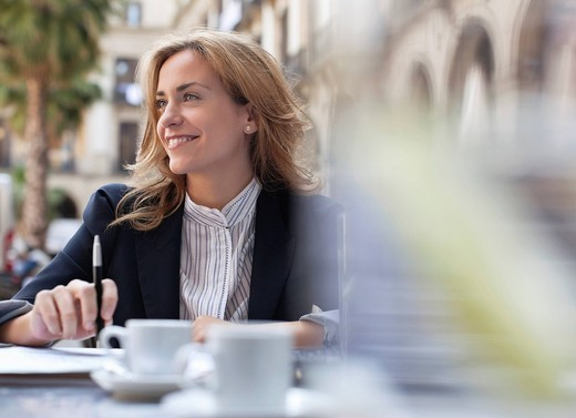 Stock Photo: 1775R-26763 Businesswoman drinking coffee in sidewalk cafe