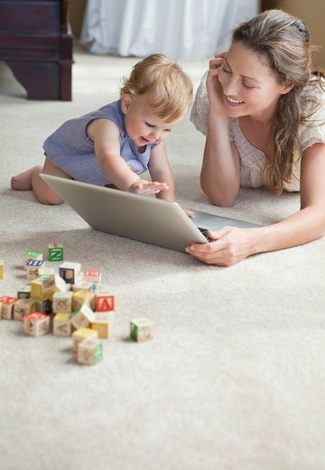 Stock Photo: 1775R-26939 Mother and daughter using laptop on floor