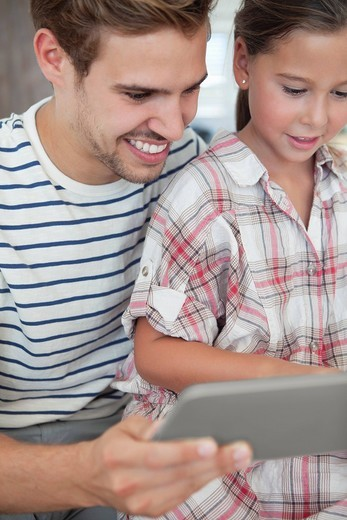 Father and daughter using digital tablet together : Stock Photo
