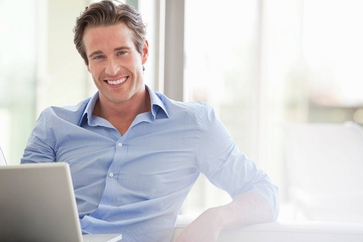 Stock Photo: 1775R-26963 Smiling man sitting with laptop